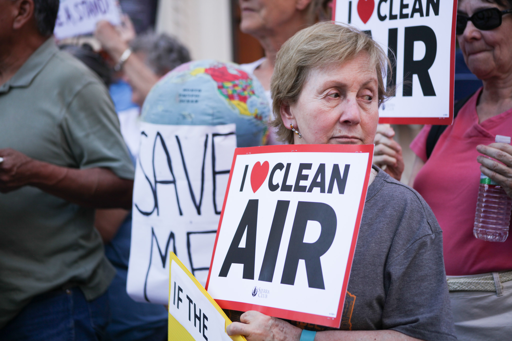 """Supporters hold up signs stating """"I love clean air"""" at the rally for the Paris climate accord."""