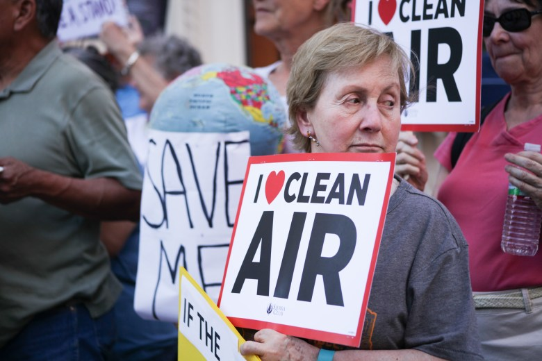 "Supporters hold up signs stating ""I love clean air"" at the rally for the Paris climate accord."