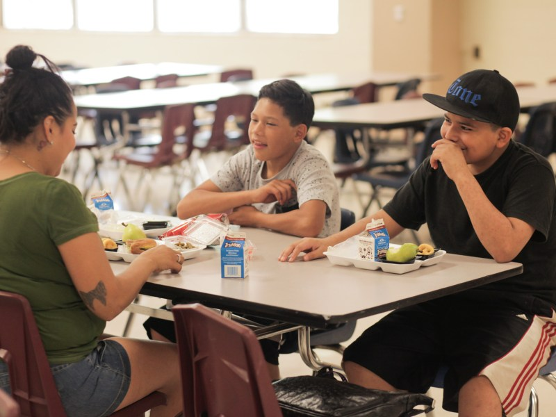 Community members laugh and enjoy food at the summer food program at Rhodes Middle School.