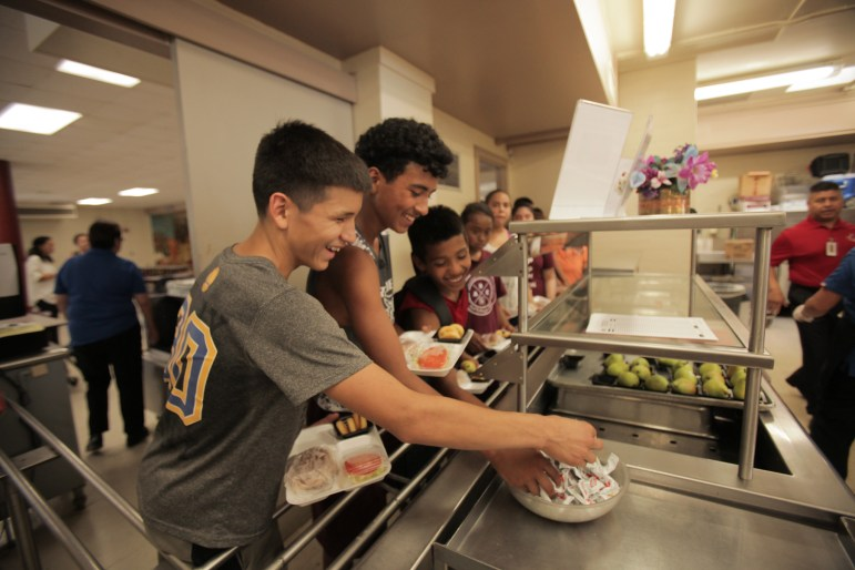 Students grab ketchup packets in the food line at Rhodes Middle School.