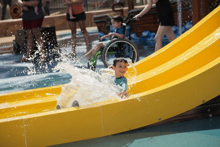 A boy enjoys the waterslide at shipwreck mountain at the new waterpark Morgan's Inspiration Island.
