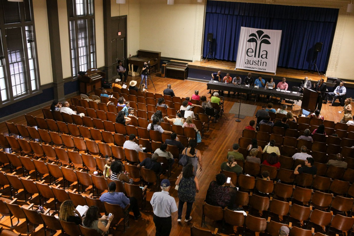 Community members file into their seats at the auditorium at Ella Austin.