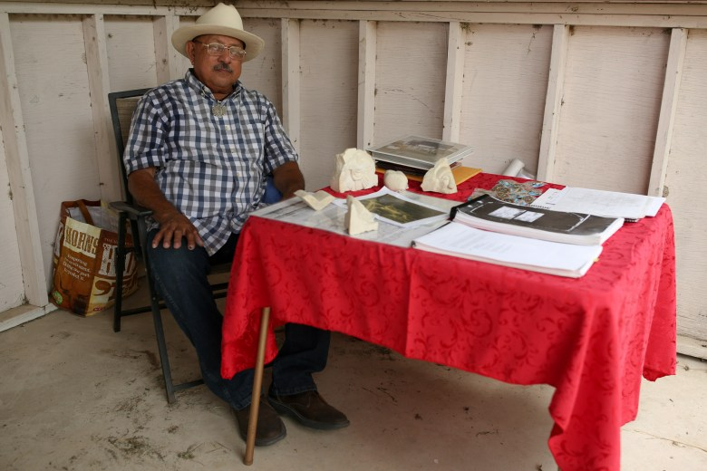 Vincent Huizar sits behind a table filled with historic documents containing proof of hid ancestor Pedro Huizar whom he recognizes as the artist behind the historic rose window at Mission San Jose.