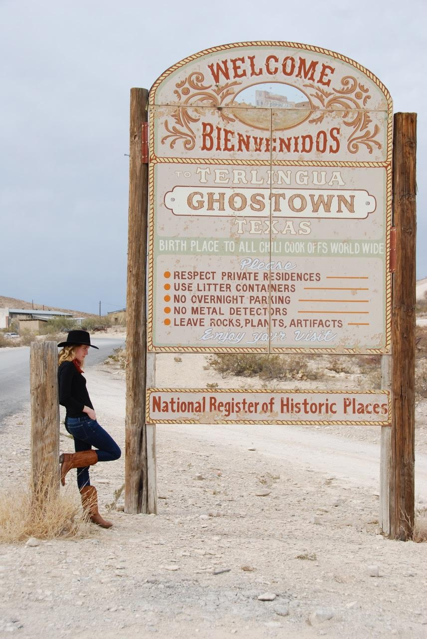 The author poses next to a welcome sign to Terlingua.
