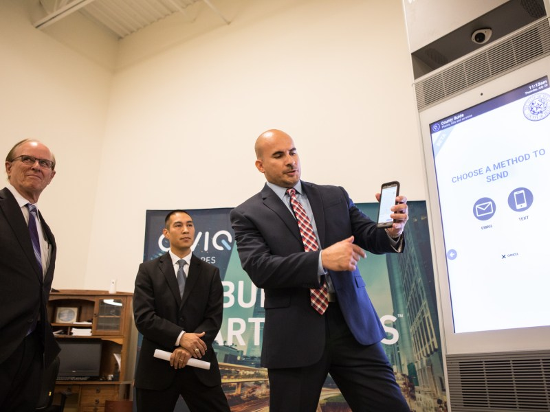 Bexar County IT Project Manager Phillip Rico (right) demonstrates how the CIVIQ Waypoint Kiosk communicates with his phone next to (from left) Bexar County Judge Nelson Wolff and Office of the County Manager Chief of Staff Thomas Guevara.