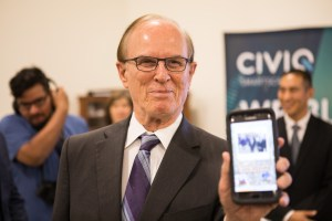 Bexar County Judge Nelson Wolff holds up his smart phone after connecting it with the CIVIQ Waypoint Kiosk.