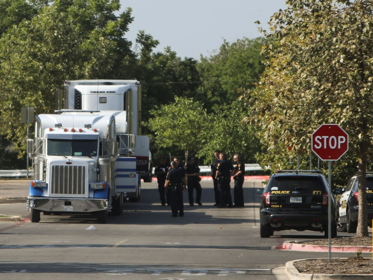 Police officers gather around the tractor-trailer and tow truck outside of Walmart.