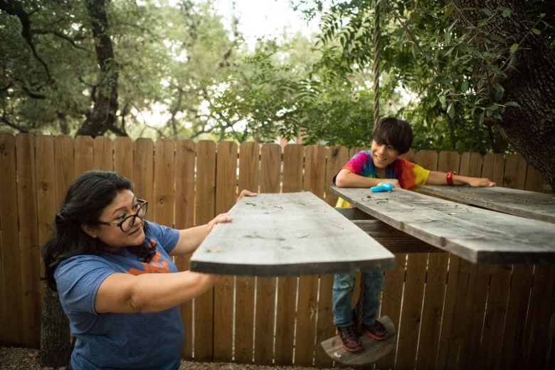Erika Prosper (left) plays with Jonah, 8, on the tree house she built by herself.