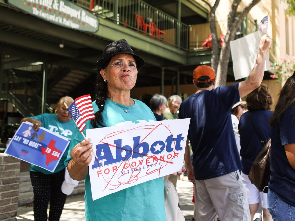 Protestors hold up signs against SB 4 and Gov. Greg Abbott outside of Sunset Station as Abbott announces his re-election campaign.
