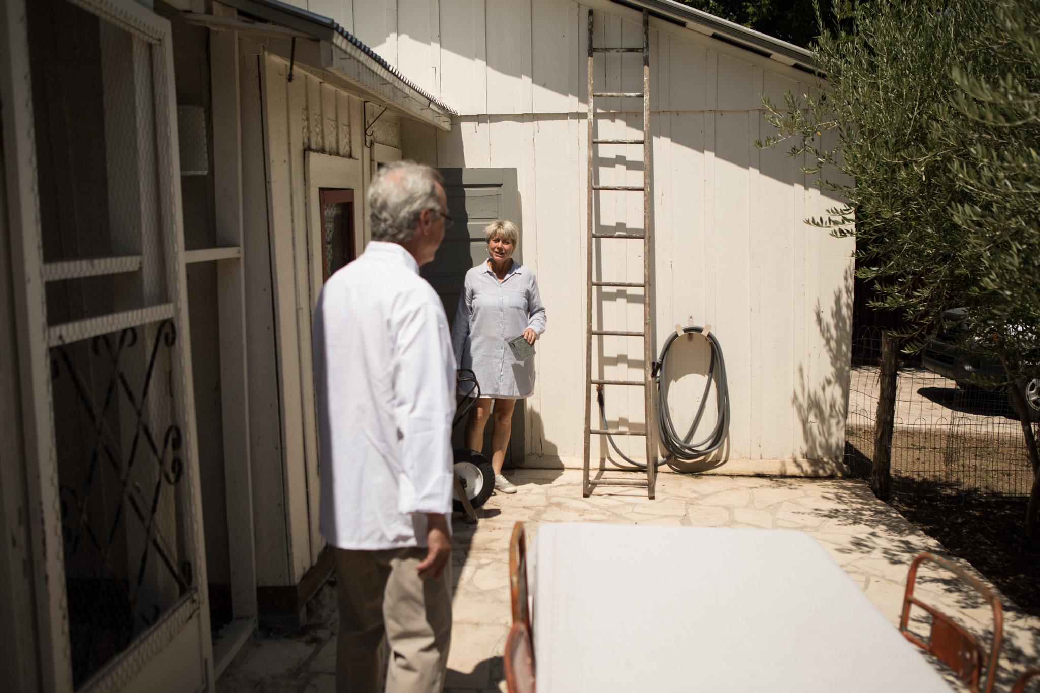 (From right) Outlaw Kitchens Co-Owners Peggy Howe and Paul Sartory chat in their backyard next to the chicken coop.