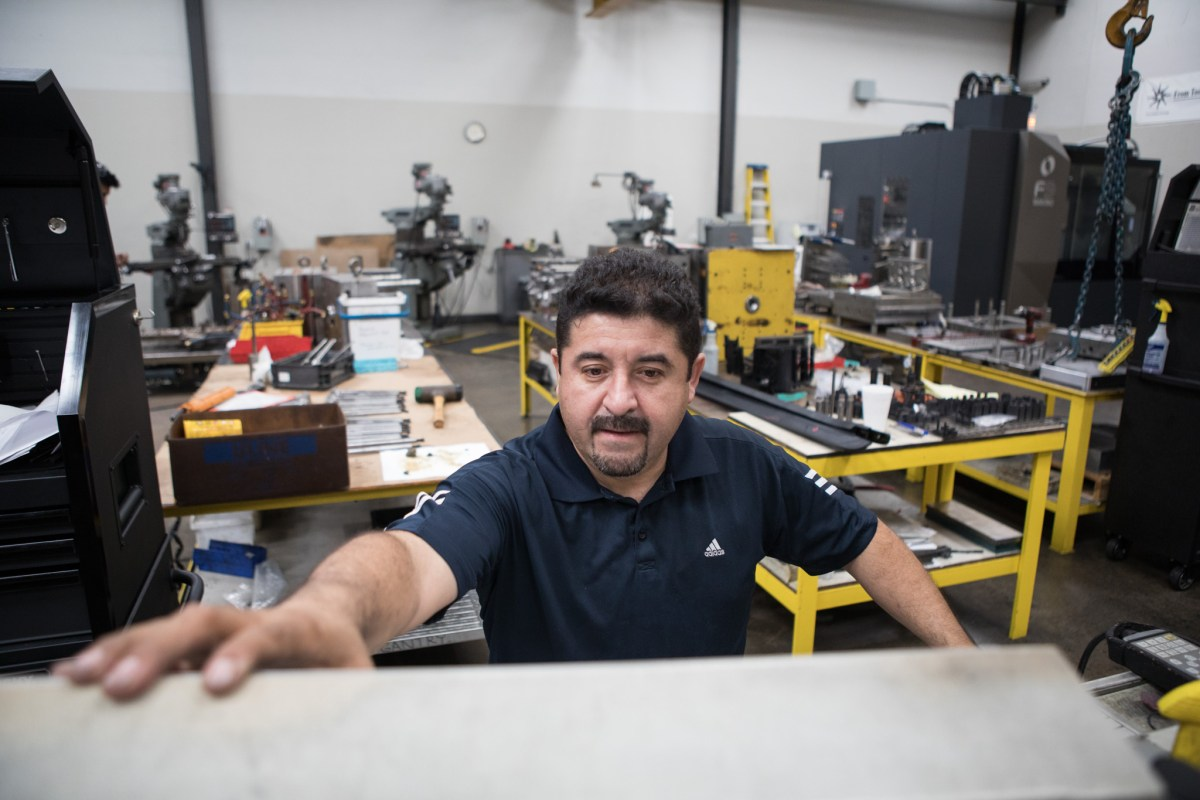 A Precision Mold & Tool Group Tool Maker Ernesto Gonzalez operates the Electrical Discharge Machine (EDM).