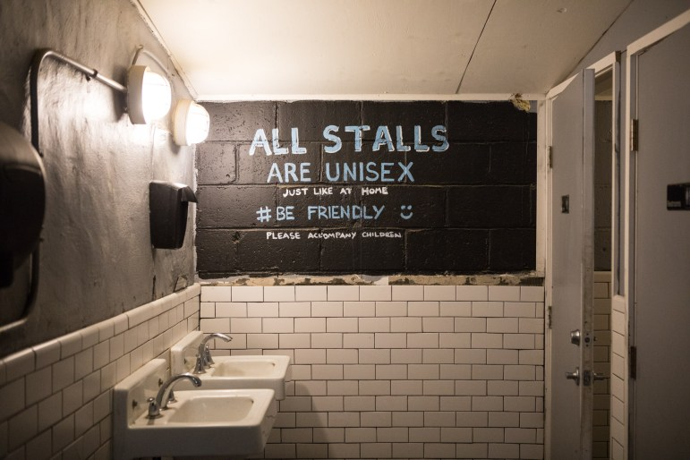 A sign in the bathroom of The Friendly Spot states that all stalls are unisex.