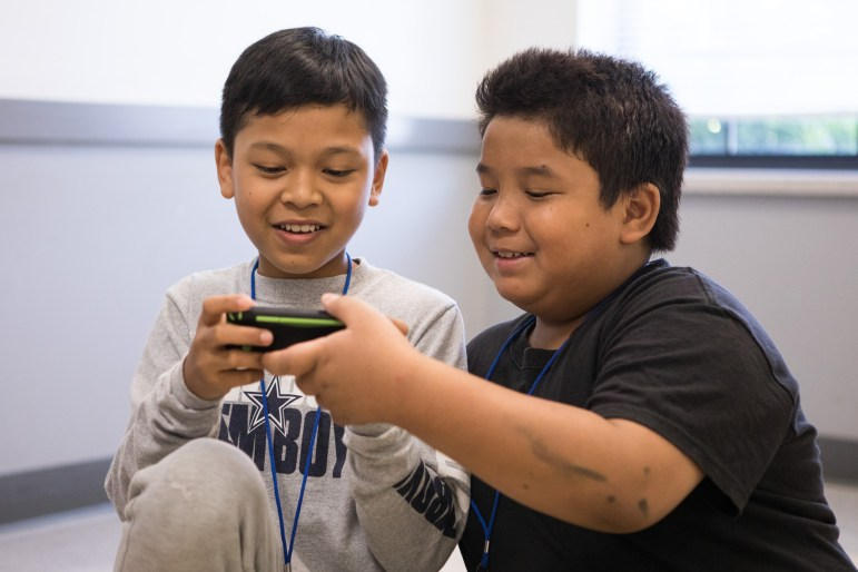 (From left) William, 11, and Pleh, play a video game while waiting for the van to take them home from camp.
