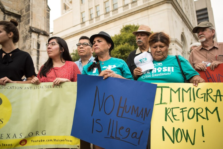 A crowd gathers with pro-immigration reform signs at the vigil for migrant deaths at San Fernando Cathedral.