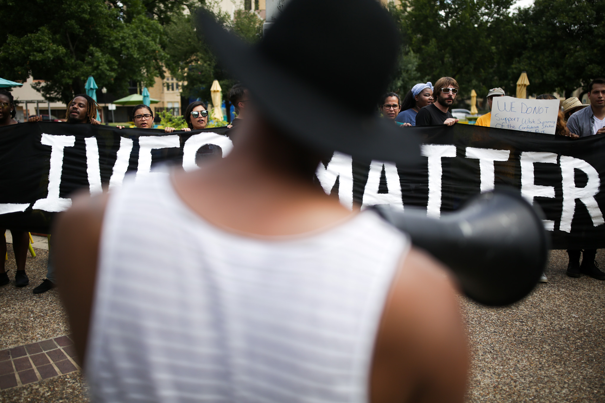 "Protestors hold up a large banner that reads 'Black Lives Matter."""