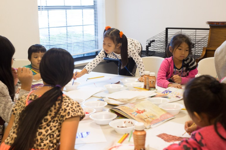 (center) Natalia, 5, reaches over to dip her watercolor brush in a bowl of water.