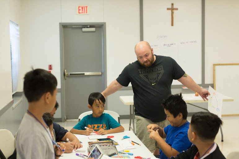 Camp leader David Haston works with students during a lesson on pollution.