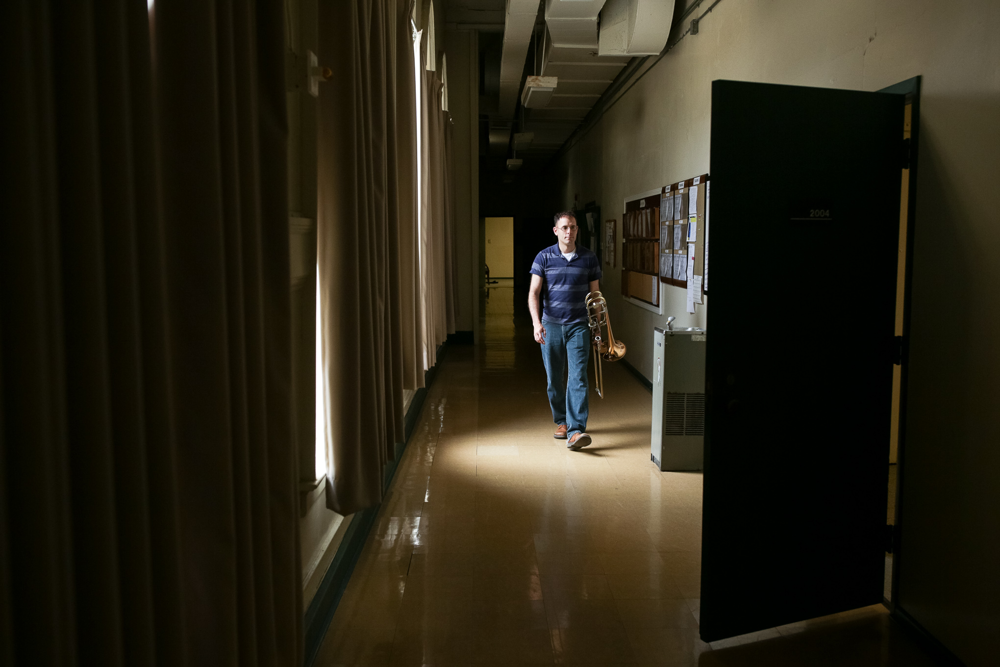 Sgt. Jonathan Stoby carries his trombone through the hallway just before the beginning of rehearsals.