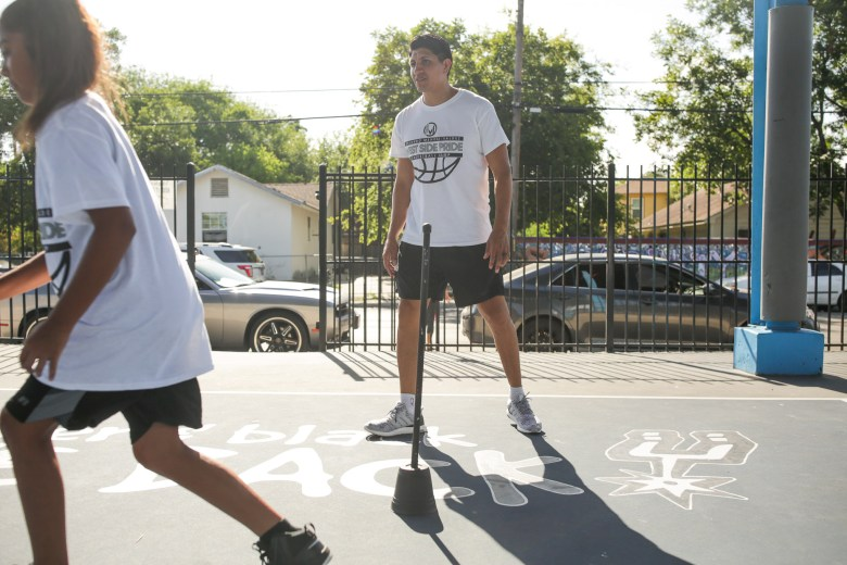 Professional basketball player Orlando Mendez-Valdez instructs campers through dribbling drills.