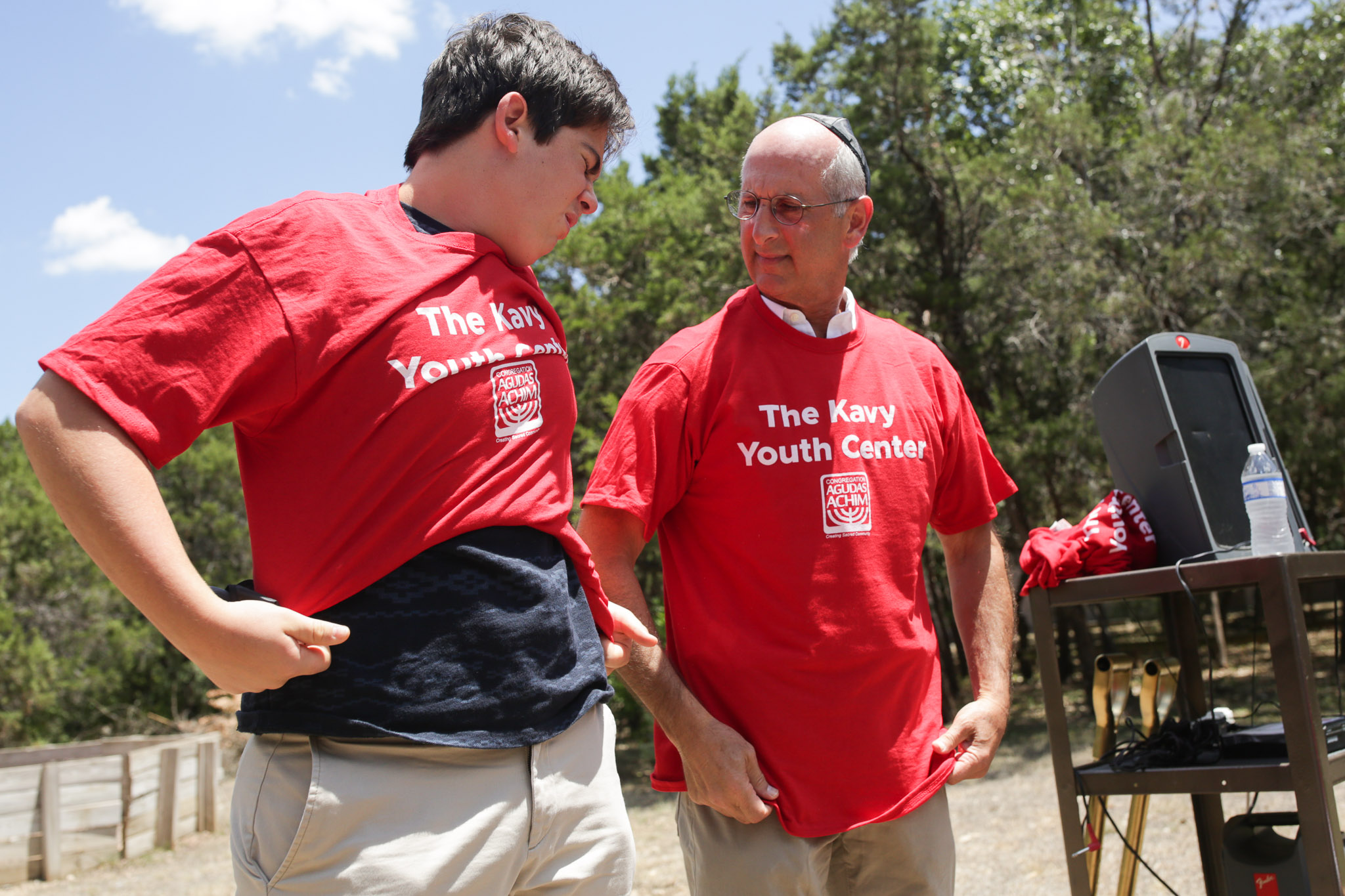 Will (left) and Jeff Kavy put on shirts honoring the groundbreaking of the Kavy Youth Center.