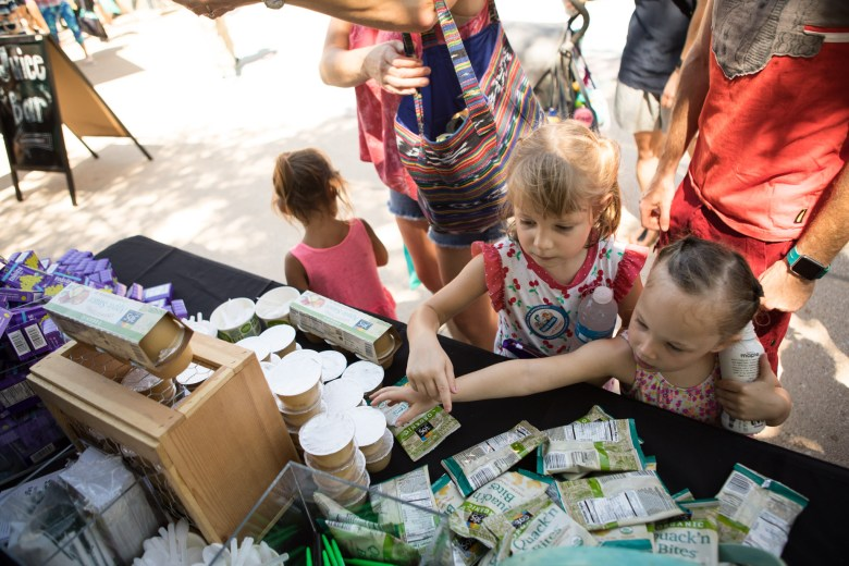 (From left) Emily, 5, and Kylie, 4, grab some snacks provided by Whole Foods Market at the Back to School Bash in Hemisfair Park.