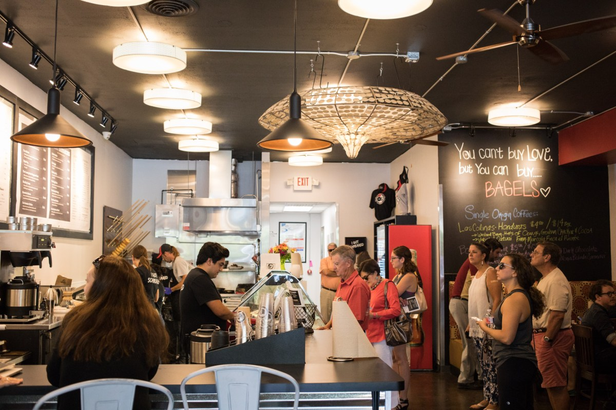 A large crowd waits in line to order on the opening day of Boss Bagel.