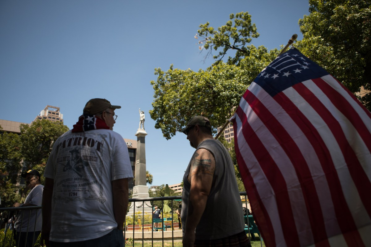 (From left) Robert Vernon and Stormy McDonald stand in opposition to the removal of the Confederate monument in Travis Park.
