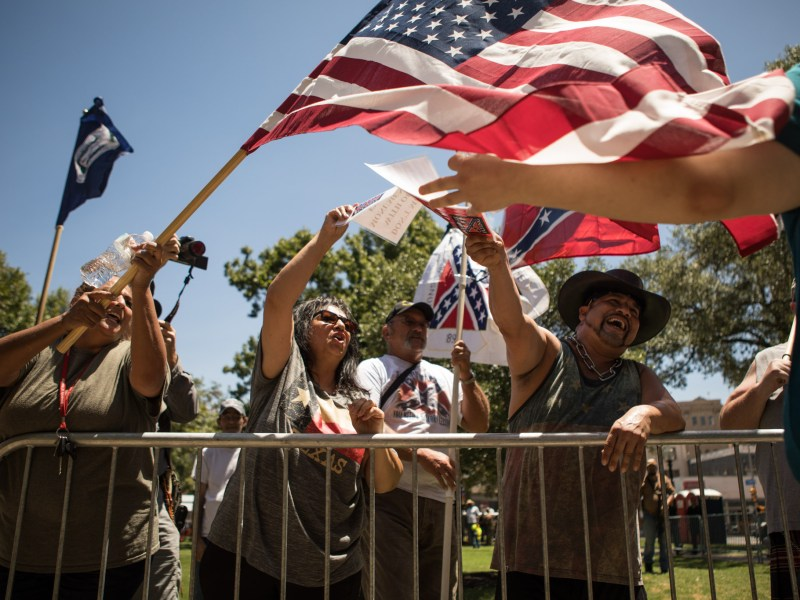 Demonstrators in opposition of the removal of the Confederate monument in Travis Park wave those outside of the fence away with their flags.