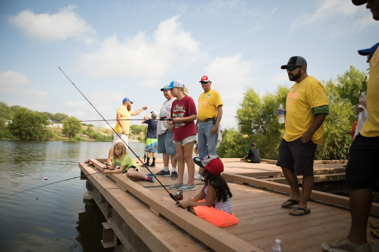 A group of Fin Addict Angler Foundation volunteers and participants in the event fish at Family, Fishing and Friends at Acequia Park.