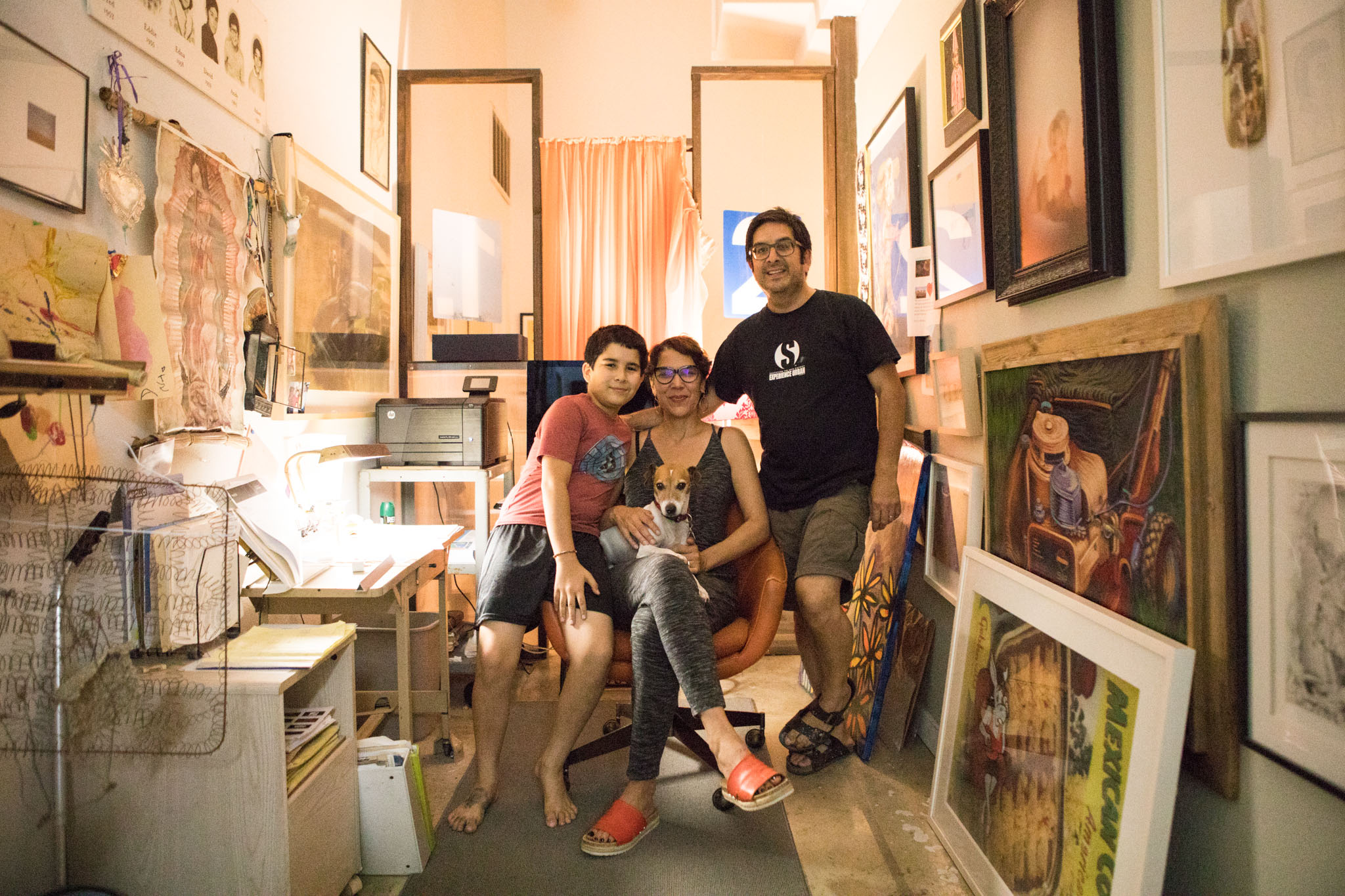 (From right) Andy Benavides, Yvette Benavides, Jake the dog, and Agusto, 11, sit in Andy's office in their home in 1906 Studio on Second Saturday.