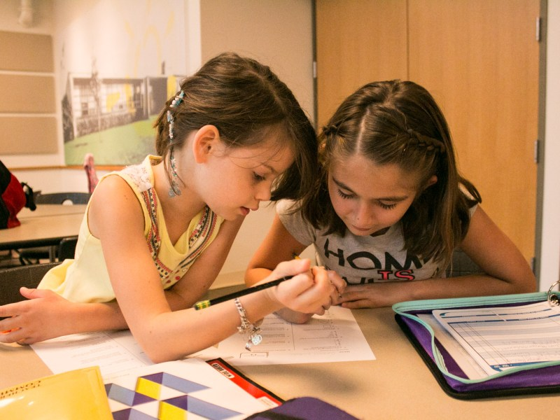(From left) Ella, 8, and Genesis, 9, complete their homework together at the YMCA After School Care Program at the Sunshine Cottage School for Deaf Children.