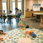 The younger group of children draws mermaids together at the YMCA After School Care Program at the Sunshine Cottage School for Deaf Children.