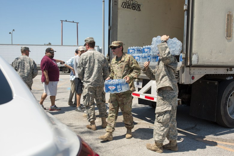 The United States National Guard carries cases of water to families in need in Aransas Pass, Texas.