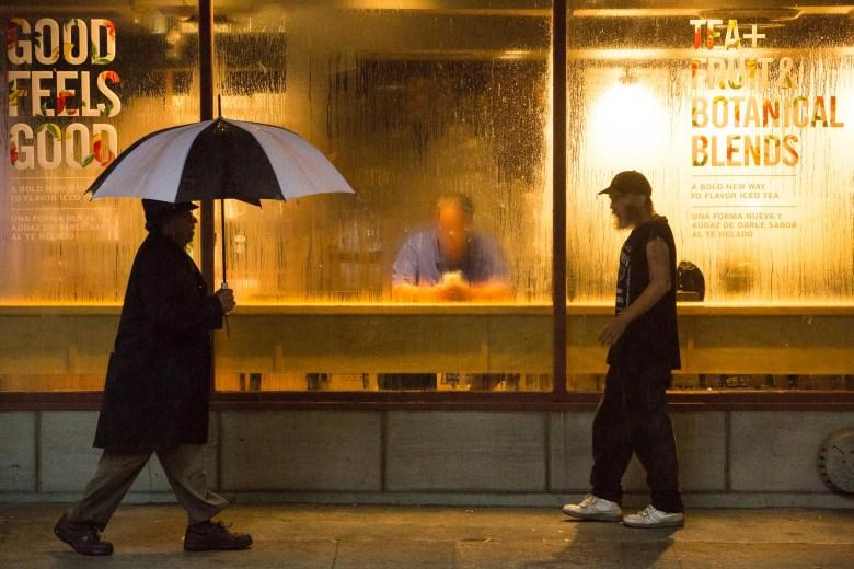 Pedestrians walk along Saint Mary's Street in front of Starbucks Coffee.