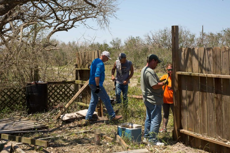 (from left) Rockport residents Kim Leblanc, James Sammons, Kevin McDonald, and Tanya Trahan work together to mend a fence on Sammon's property.