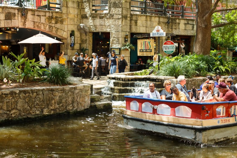 A river barge passes Rita's On the River on the San Antonio River.