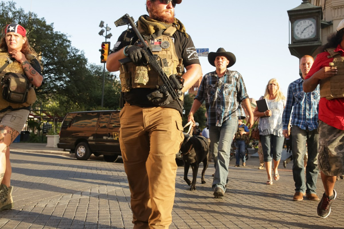 Brandon Burkhart (center) is escorted with fellow membetrs of TITFF (This is Texas Freedom Force) following Citizens to be Heard at City Council on Wednesday evening.