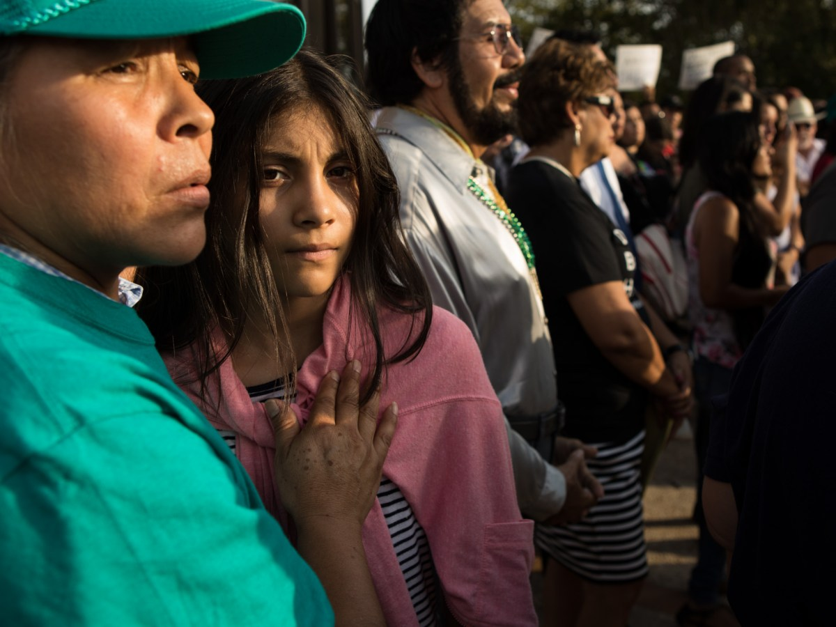 (From left) Juana Arellano and Casandra de Leon hold one another while listening to speakers protest the Trump administration's decision to end DACA.