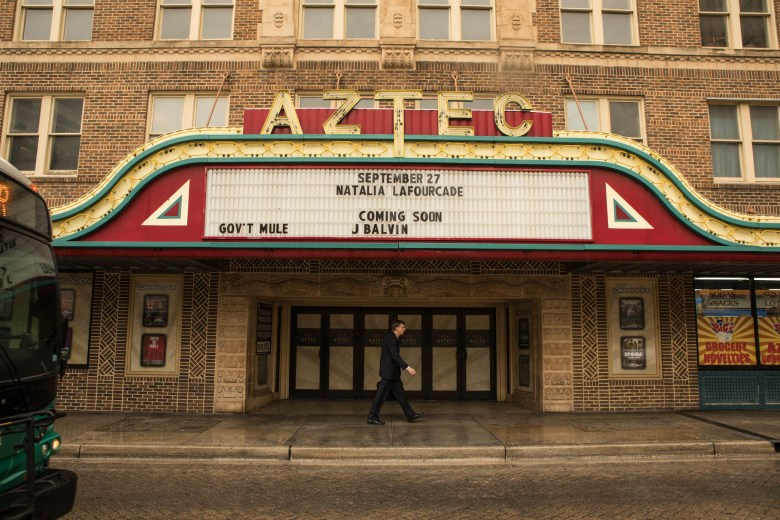A man walks in front of the Aztec Theatre.