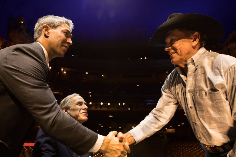 (From left) Mayor Ron Nirenberg and Gov. Greg Abbott greet George Strait at a press conference before his benefit concert at the Majestic Theatre.