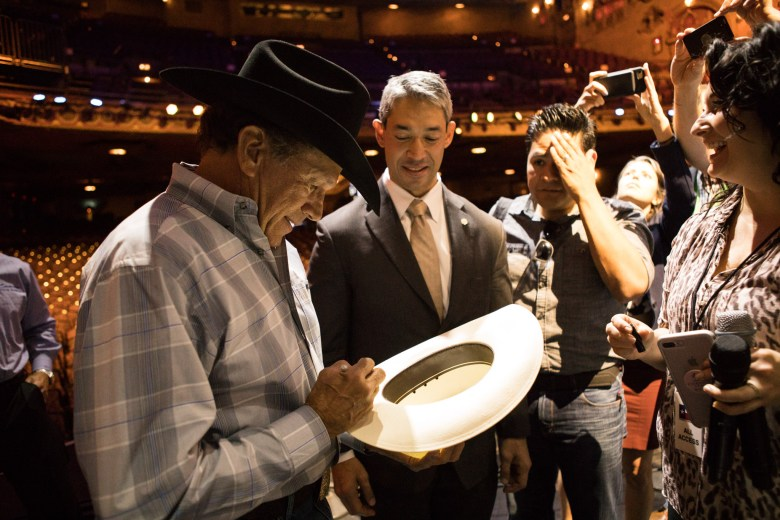George Strait signs a hat for Mayor Ron Nirenberg at a press conference before his benefit concert at the Majestic Theatre.