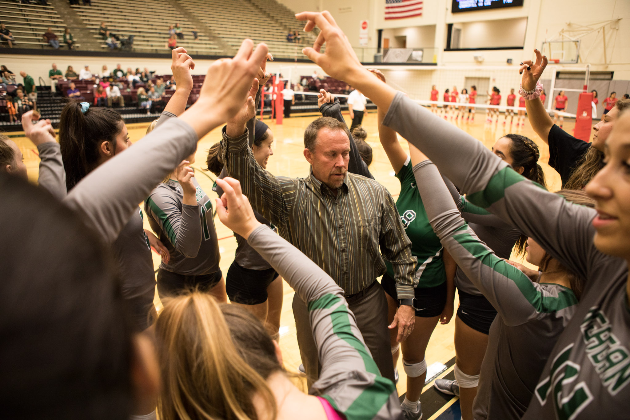 Ronald Reagan High School Volleyball Coach Mike Carter brings the Reagan Rattlers into a huddle before the match.