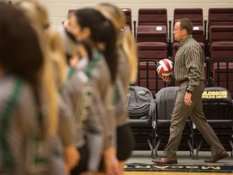 Ronald Reagan High School Volleyball Coach Mike Carter brings a volleyball back to the basket while his players are introduced.