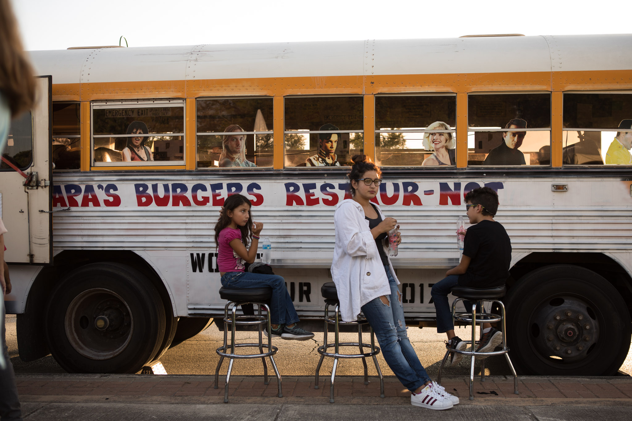 (From left) Aracely, 7, Andrea, 15, and Emilio, 9, sit outside of Papa's Burgers Restaur-not food truck at Restored By Light.