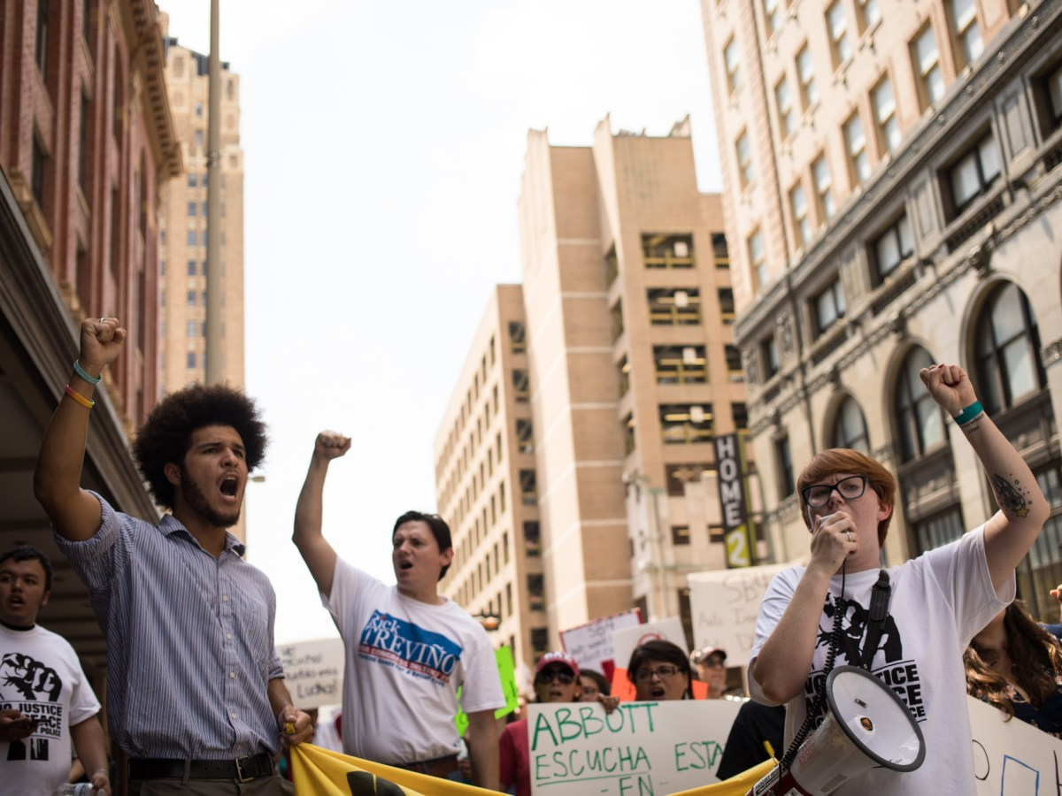 (From left) Sean Rivera, Rick Treviño, and Cole Harvey shout with their fists in the air during the protest against SB4.