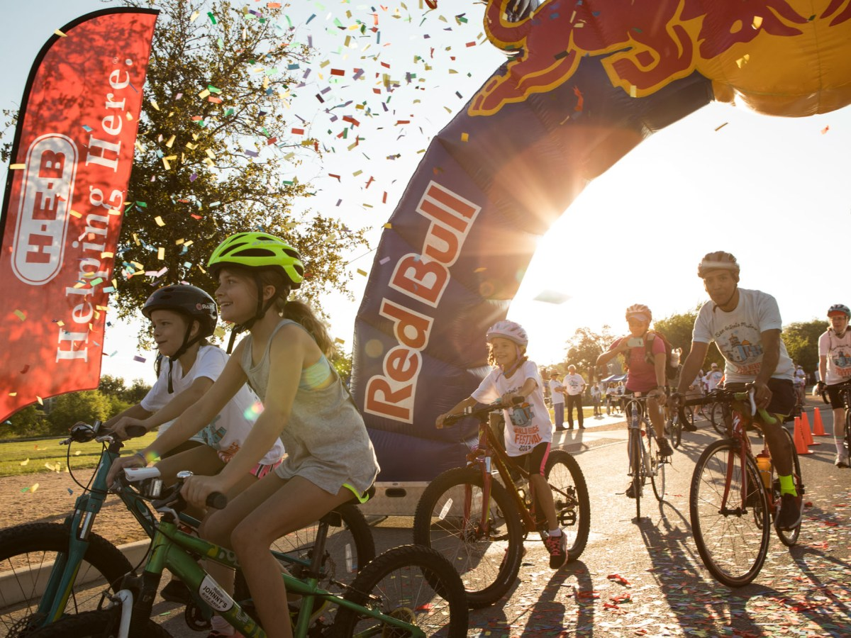 The World Heritage Tour de las Misiones bike ride participants begin their ride as confetti explodes in the air.