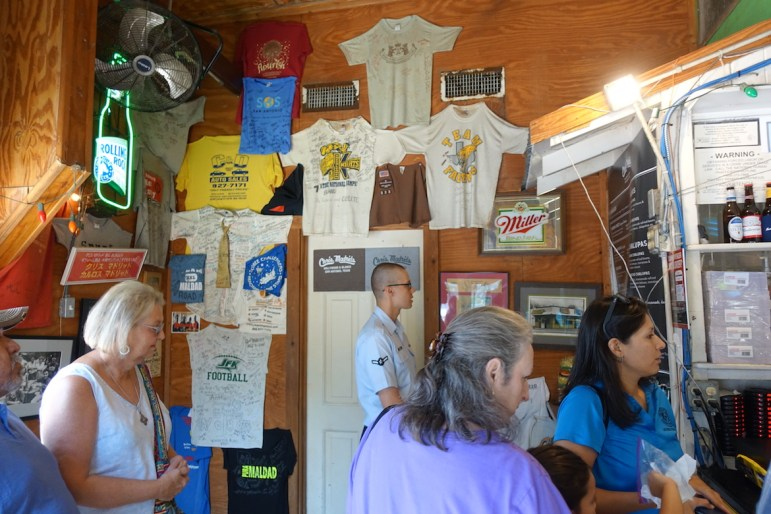 Customers line up to read the short and simple menu at Chris Madrid's. T-shirts line the walls with signatures of previous customers.