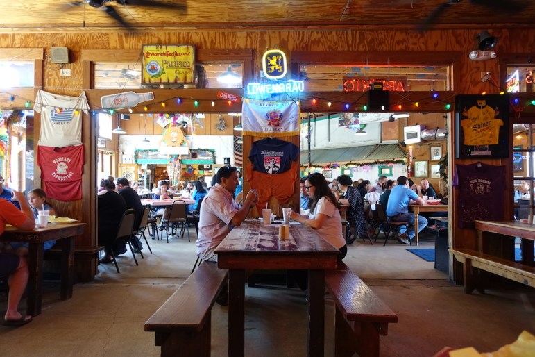 Customers dine on family-style picnic benches at Chris Madrid's.
