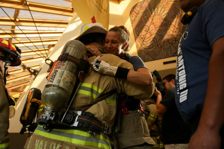 San Antonio 110 Memorial Tower Climb Founder Dawn Solinksi embraces with a fellow firefighter before he enters the tower.