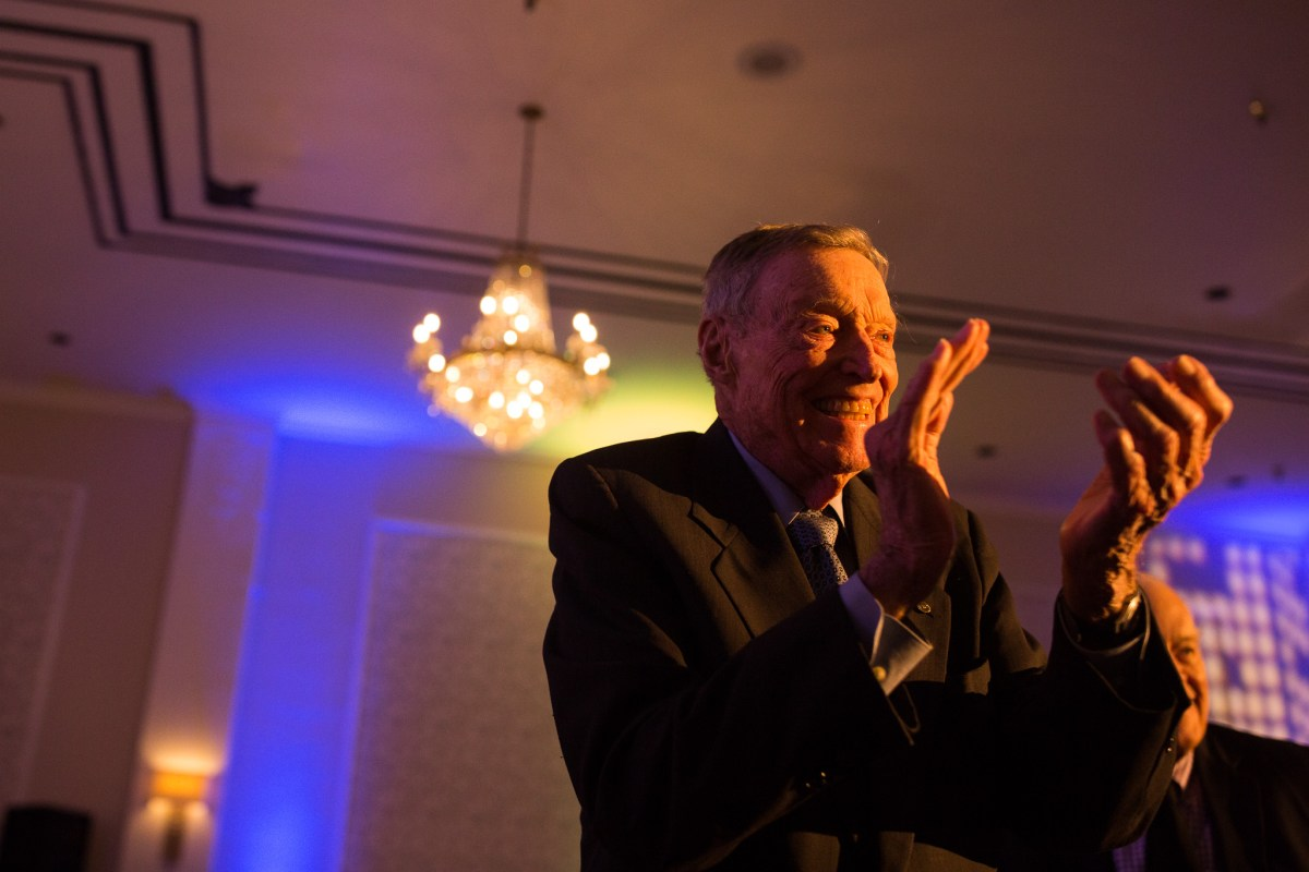 Tom Frost applauds as the surprise sound of Jim Collum's trumpet appears in the background.
